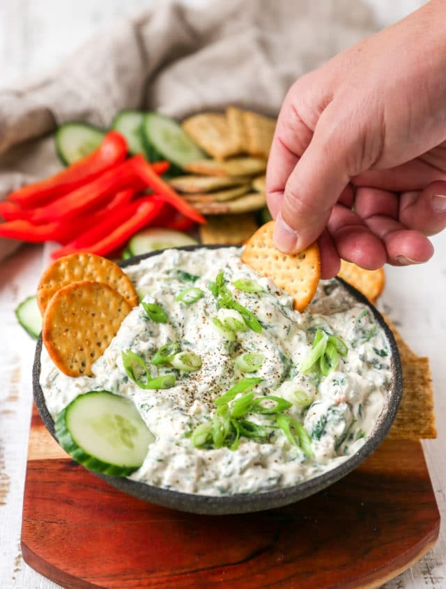 hand dipping cracker into spinach dip