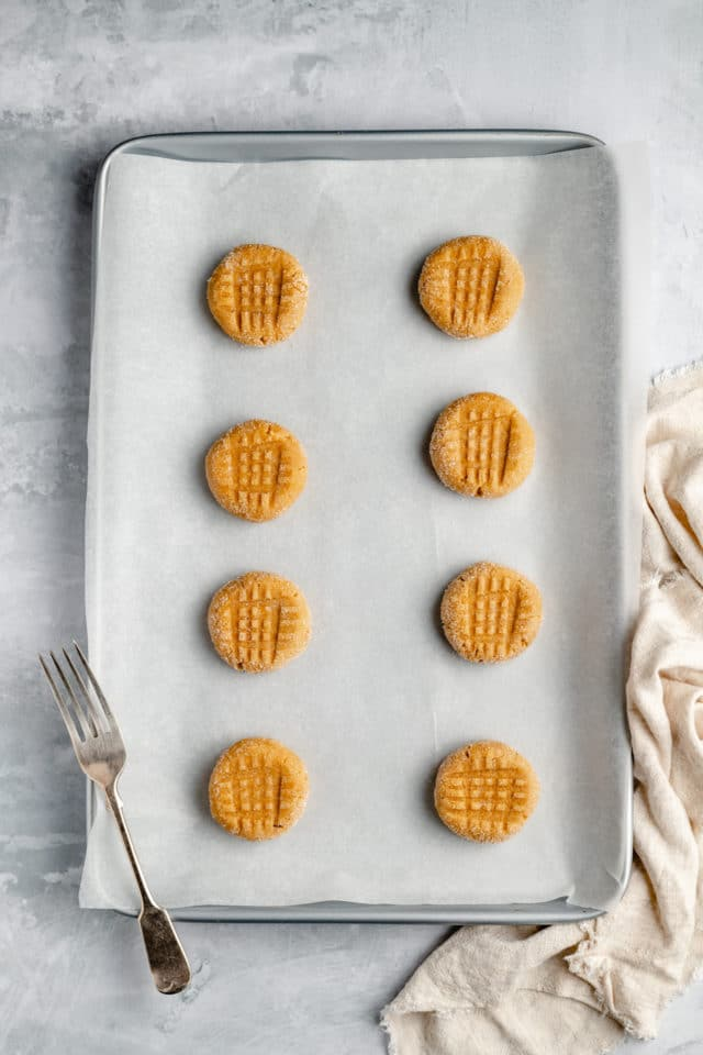 peanut butter cookie dough on a baking sheet with fork imprints on the tops