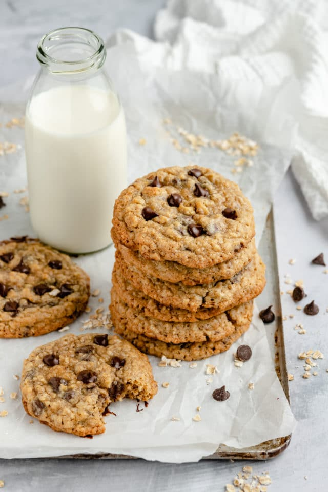 chocolate chip oatmeal cookies stacked and served with a glass of milk