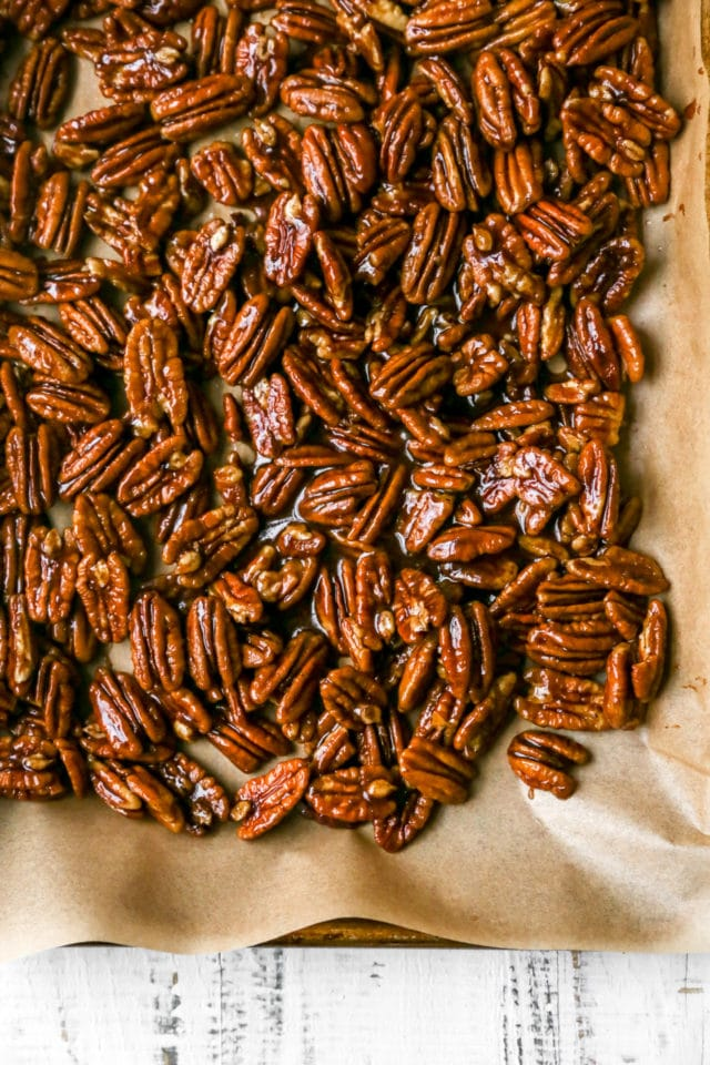 candied pecans on a baking sheet lined with parchment paper