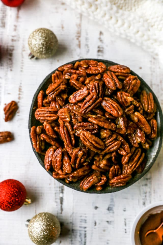 glazed pecans in a serving bowl near Christmas tree ornaments