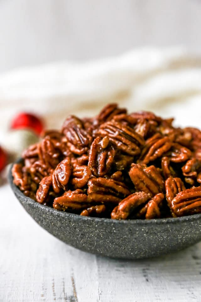 candied pecans in blue serving bowl near Christmas ornaments