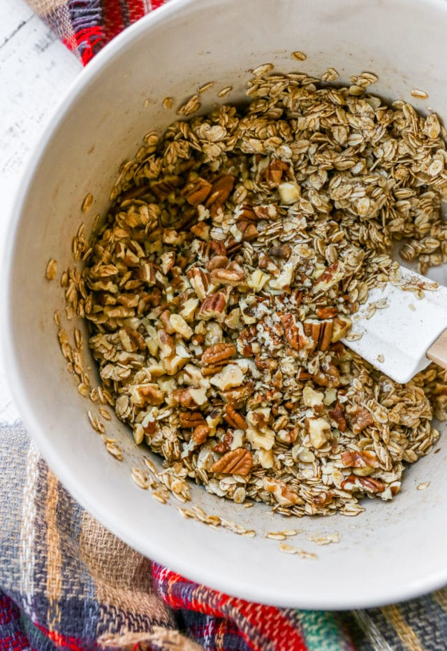 mixing oats, nuts and oil for granola recipe