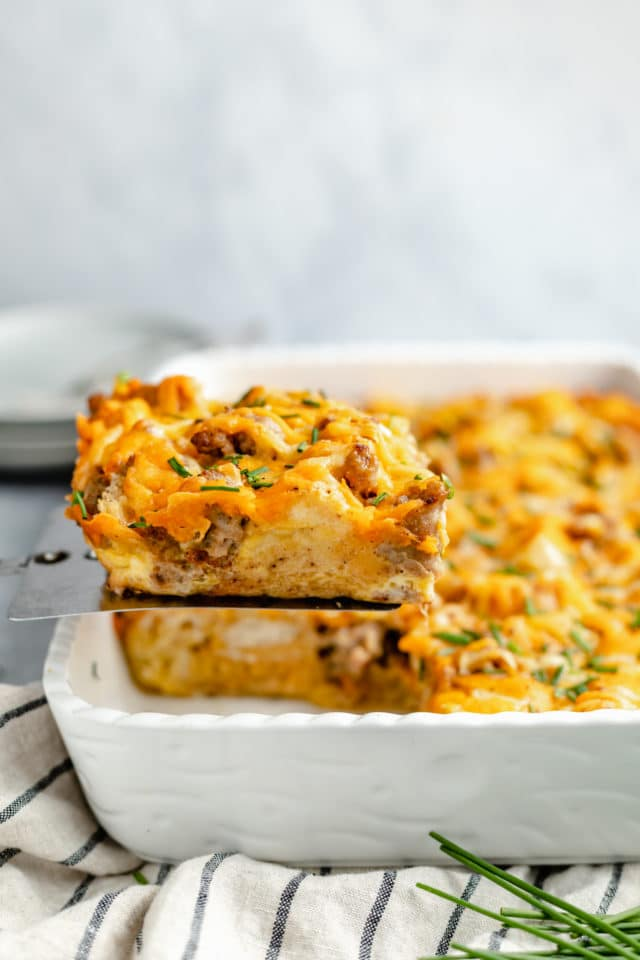 serving a slice of breakfast casserole out of a dish