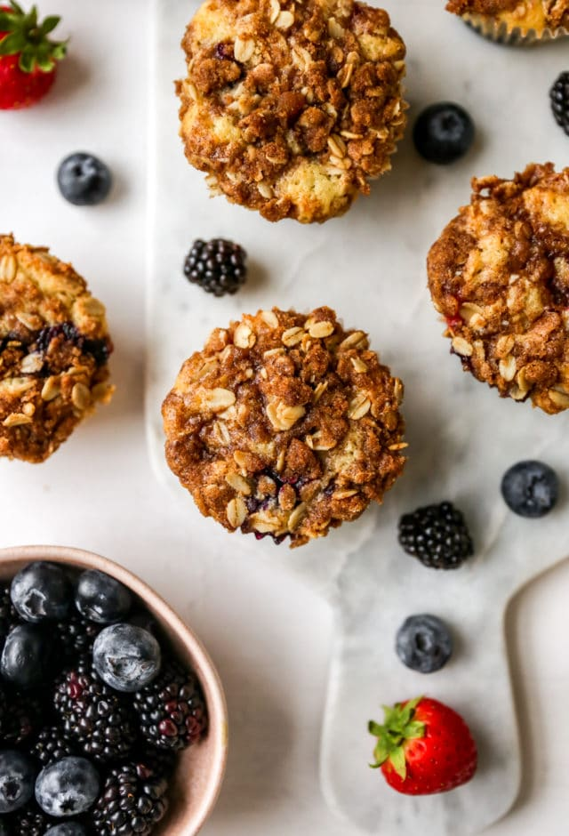 muffins with a streusel topping near blueberries, blackberries and strawberries