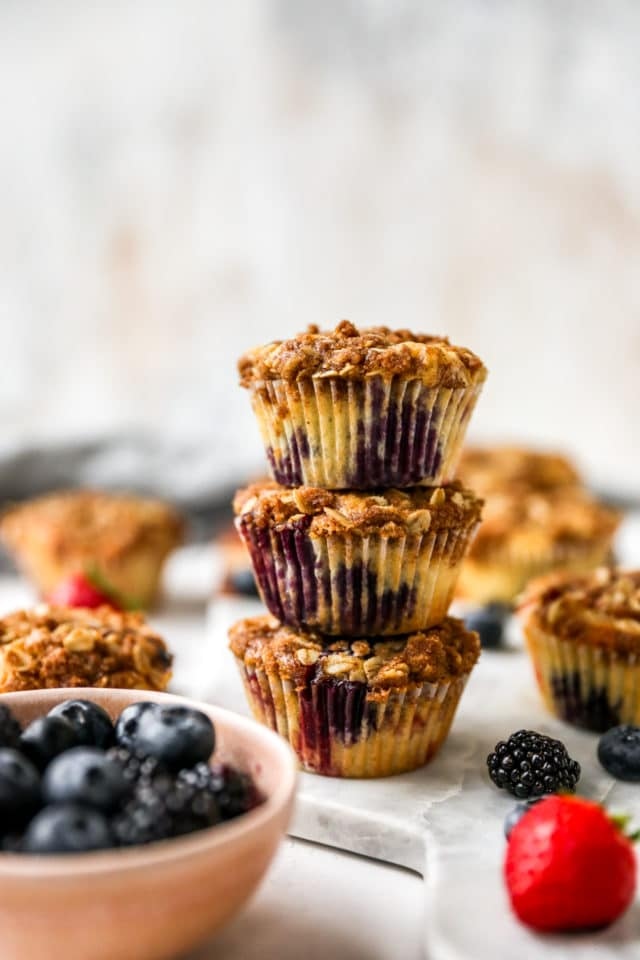 three berry muffins stacked near fresh blueberries