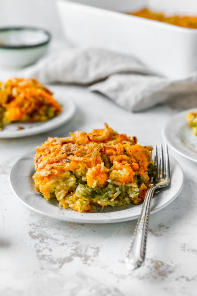 serving of broccoli rice casserole on a small white plate with a fork