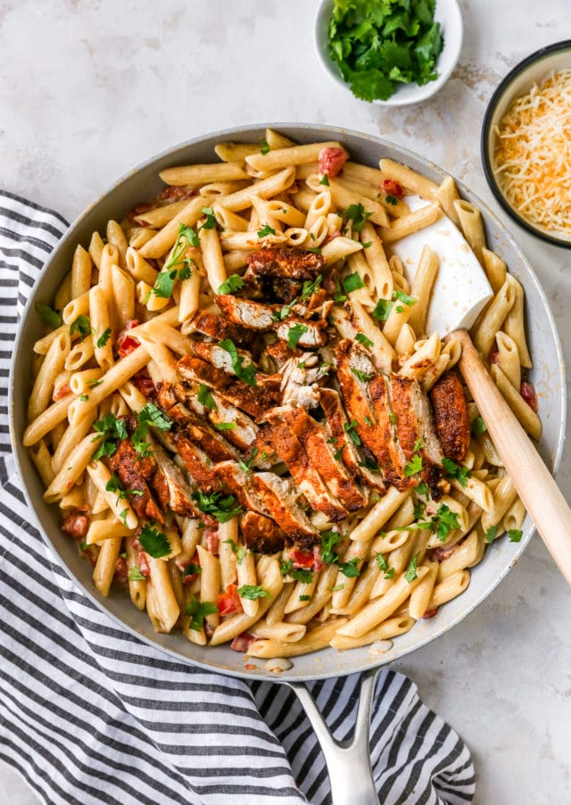 stirring pasta and chicken in a skillet