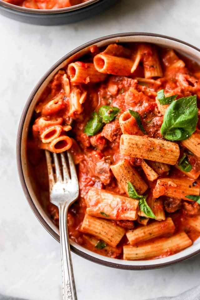 fork in a bowl of pasta in a creamy tomato sauce
