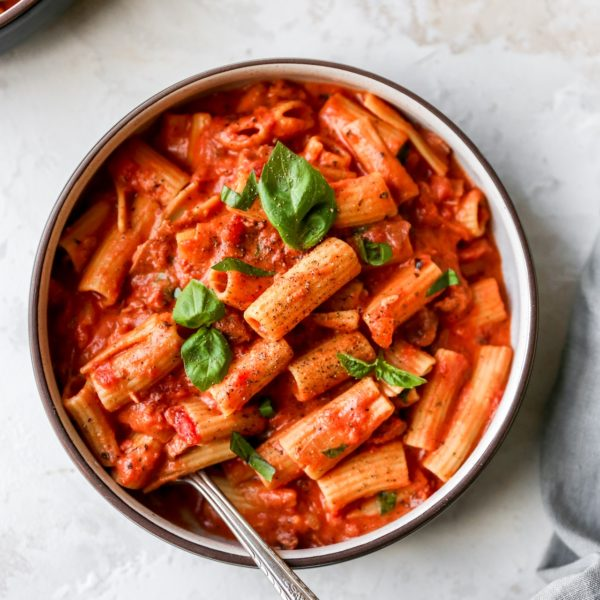creamy pasta sauce over rigatoni pasta and topped with fresh basil