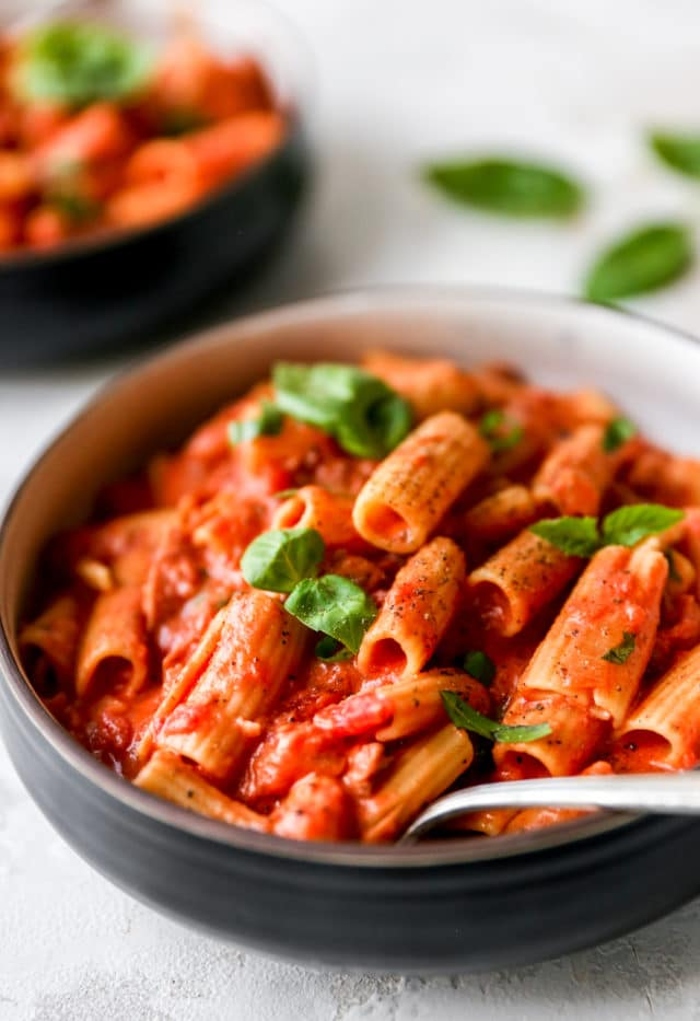 bowl filled with rigatoni and covered with a creamy tomato pasta sauce