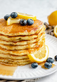 stack of lemon ricotta pancakes topped with blueberries, syrup and sliced lemon