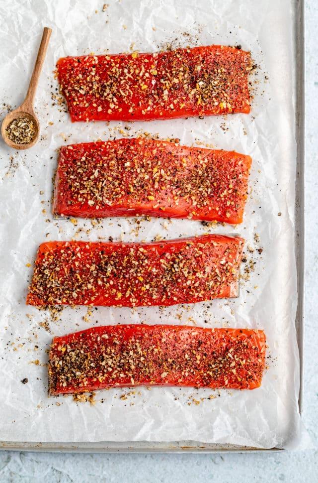 raw seasoned salmon on parchment