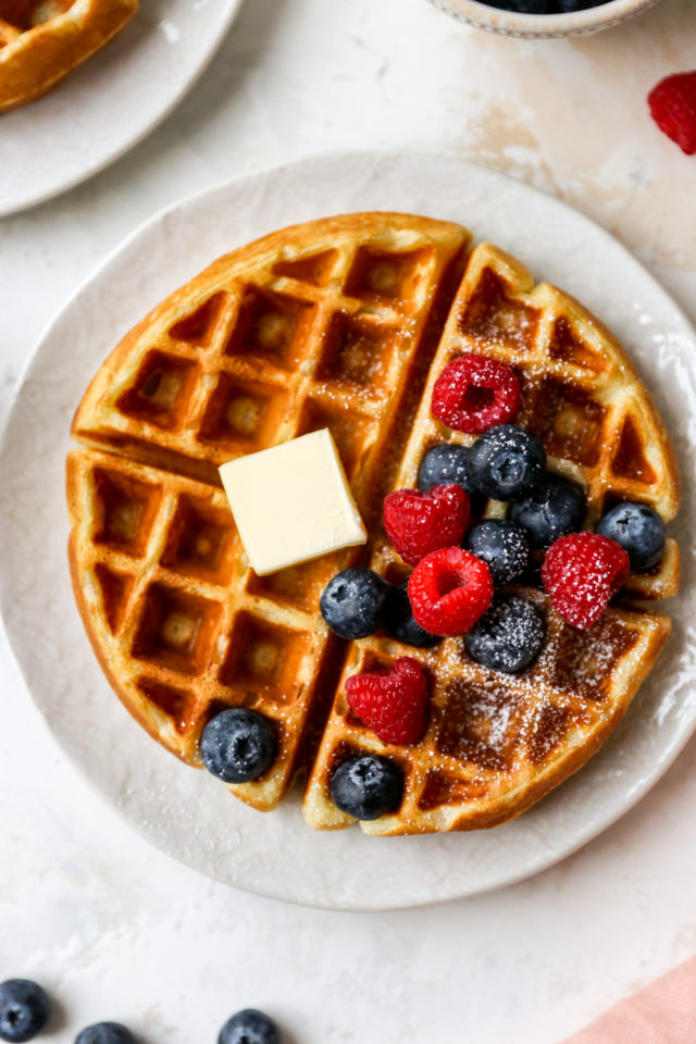 large waffle topped with butter and fruit