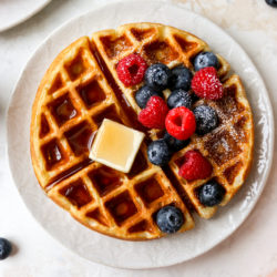buttermilk waffles served with butter, maple syrup and berries