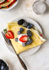 folded crepe filled with whipped cream and fresh berries