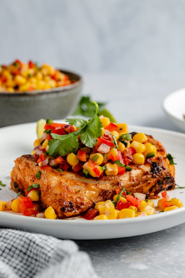 white fish served with corn salsa and fresh cilantro