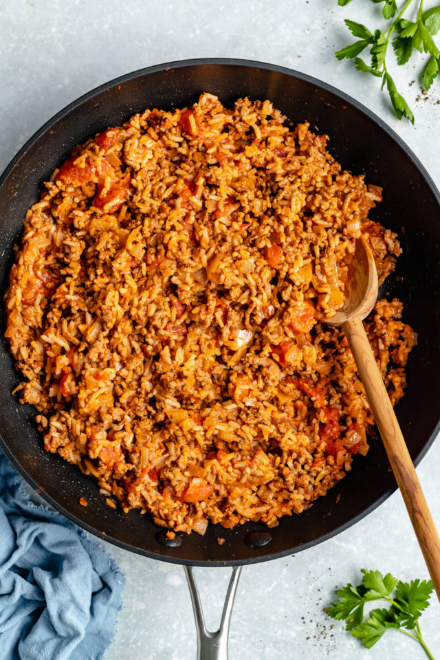 ground beef cooking with rice in a large skillet