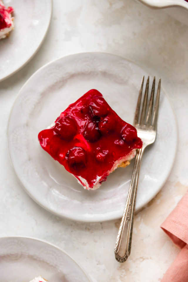 dessert topped with cherry pie filling served on a plate with a fork
