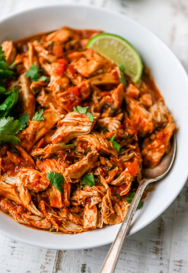 shredded salsa chicken in a white bowl with a spoon