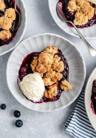 bowl of blueberry cobbler topped with vanilla ice cream