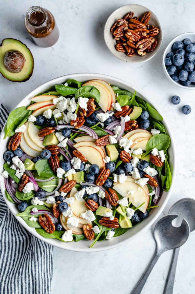 spinach salad topped with apple slices, blueberries and feta cheese