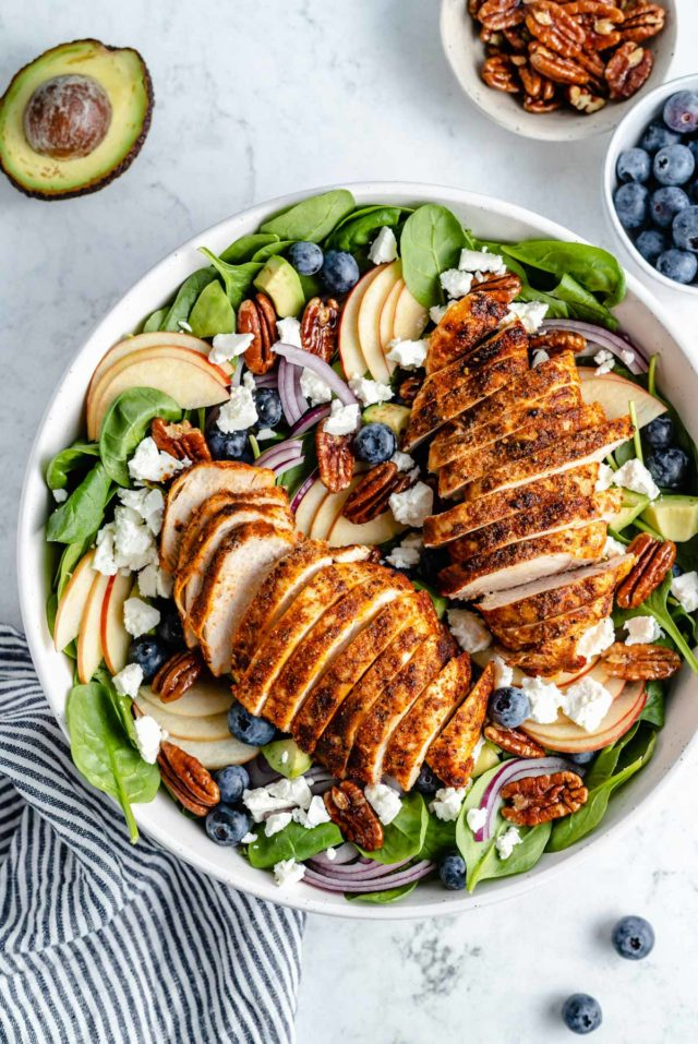 spinach salad with chicken in a large white serving bowl