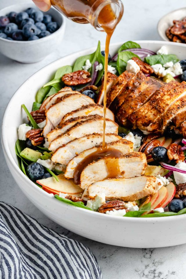 pouring balsamic vinaigrette on a salad with chicken
