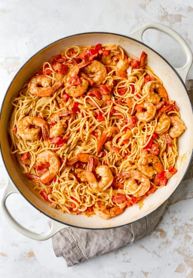 large pot with spaghetti, shrimp and diced tomato