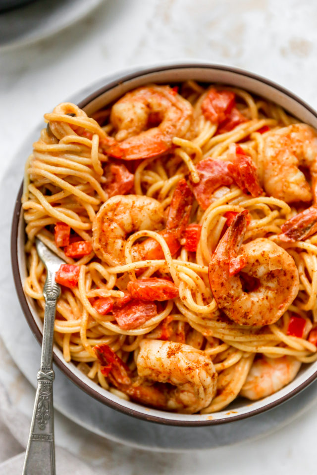 cajun shrimp pasta topped with red peppers and diced tomatoes