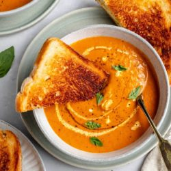 grilled cheese dipped into a bowl of roasted tomato soup