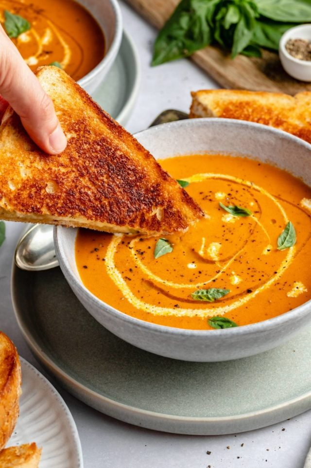 hand dipping a grilled cheese sandwich into tomato soup
