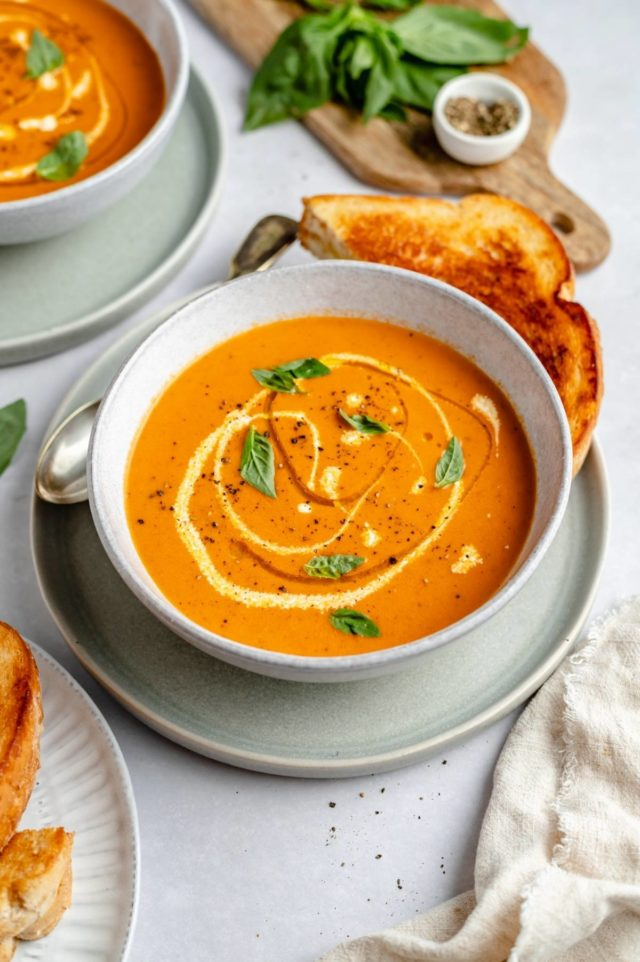 roasted tomato soup in a bowl and a grilled cheese near the bowl