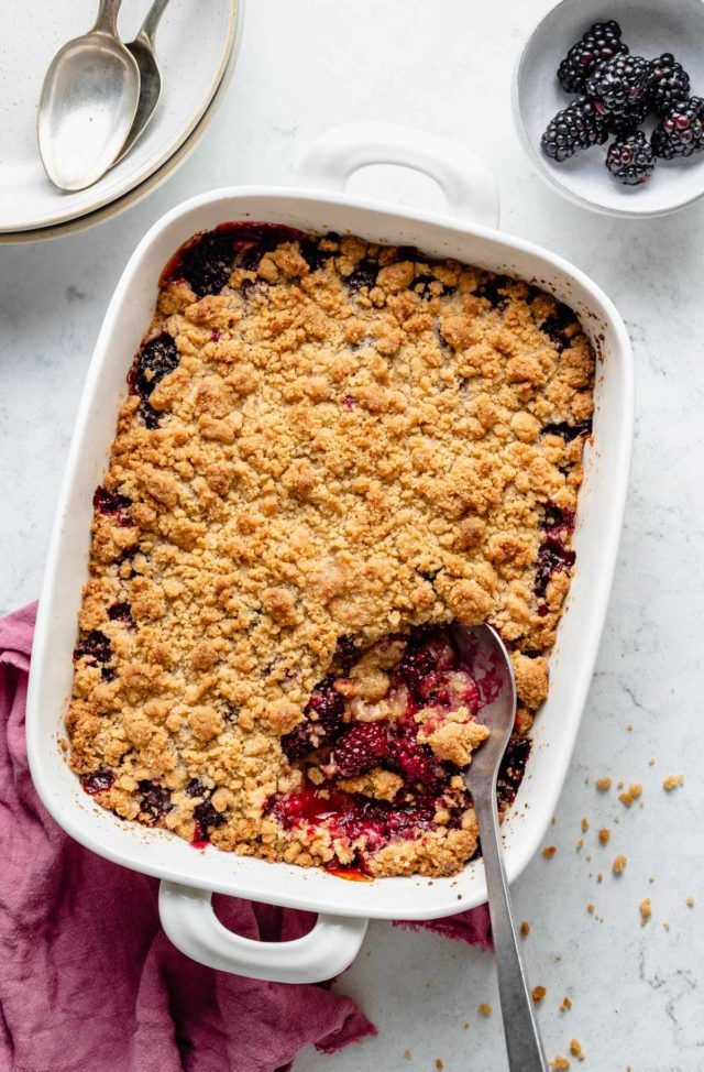 serving spoon dishing blackberry crumble from a baking dish