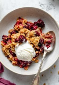 serving of blackberry crumble topped with a scoop of vanilla ice cream
