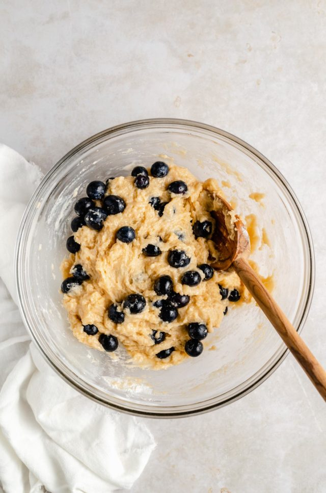mixing blueberries into muffin batter