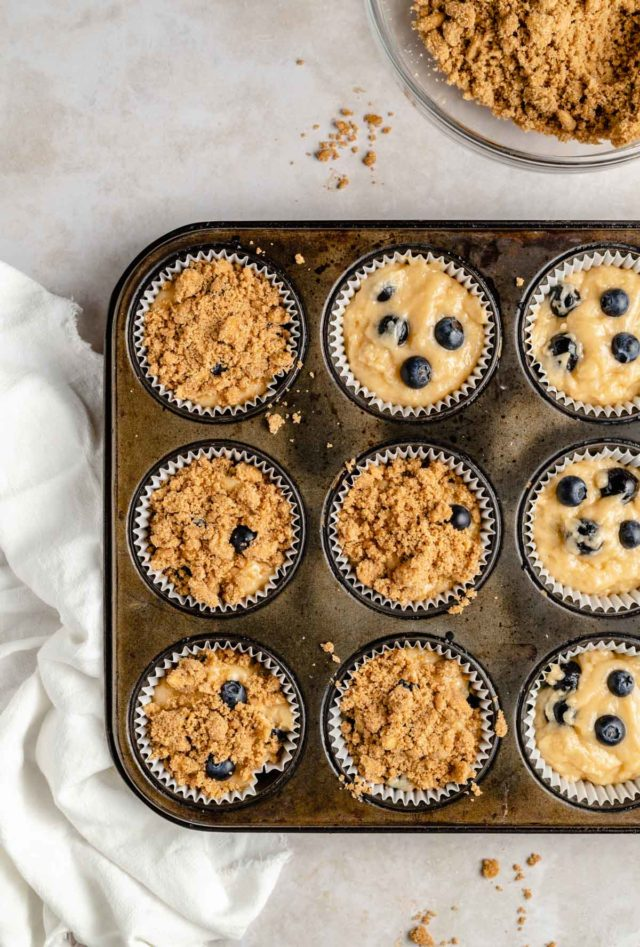 adding crumb topping to blueberry muffin batter