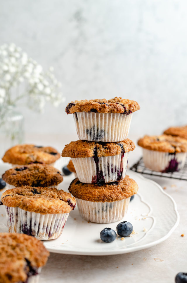 three blueberry crumb muffins stacked on a plate