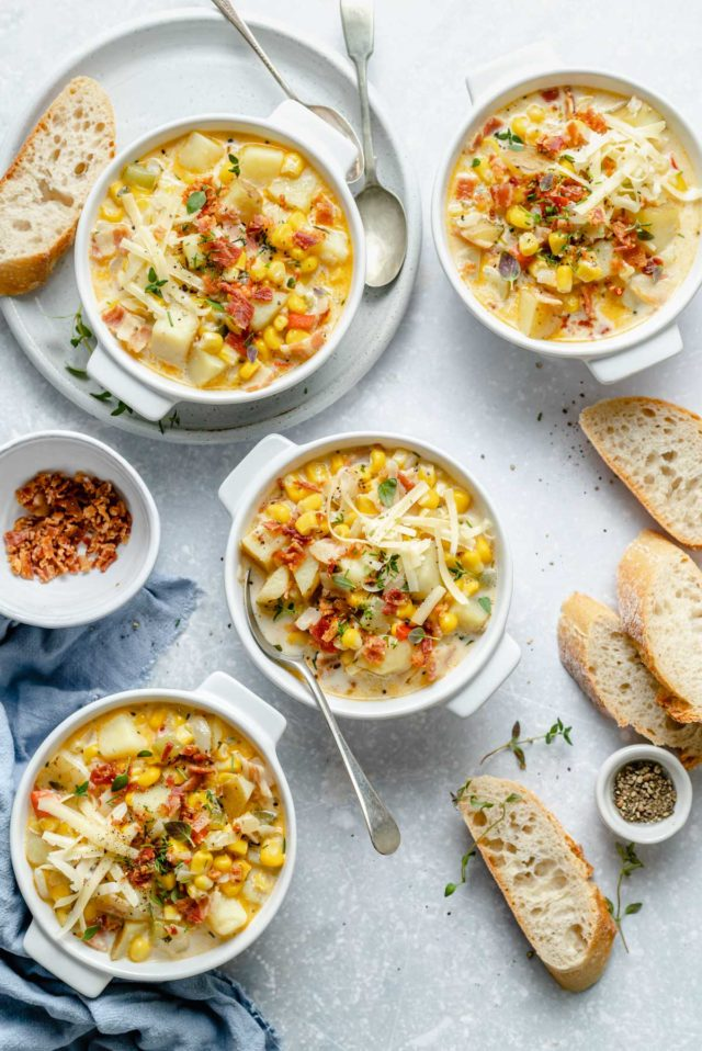bowls of corn and potato chowder served with slices of bread