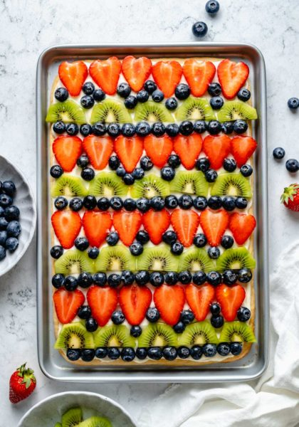 fruit pizza on a cookie crust topped with strawberries, blueberries and kiwi