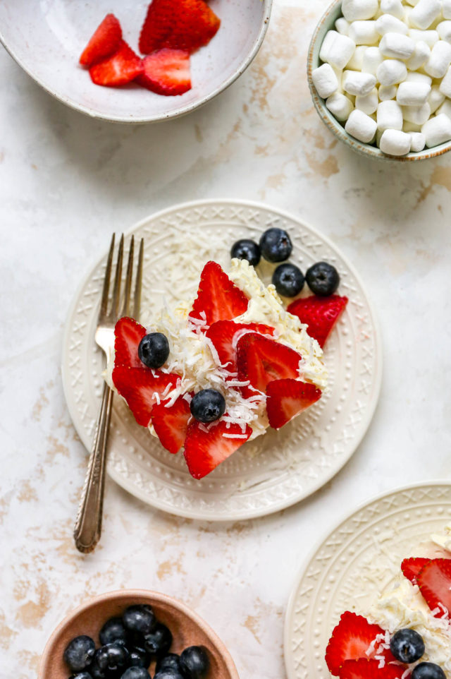 piece of yellow cake topped with strawberries, blueberries and shredded coconut