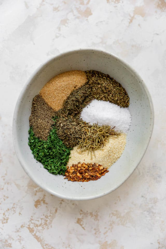 mixing a variety of spices together in a small white bowl