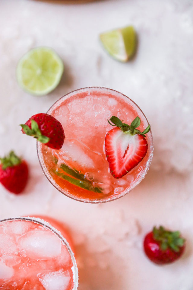 strawberry margarita in a glass with fresh strawberries and lime
