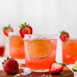 strawberry margarita garnished with lime slices and fresh strawberries