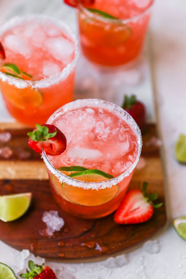 strawberry cocktail garnished with fresh lime and strawberries