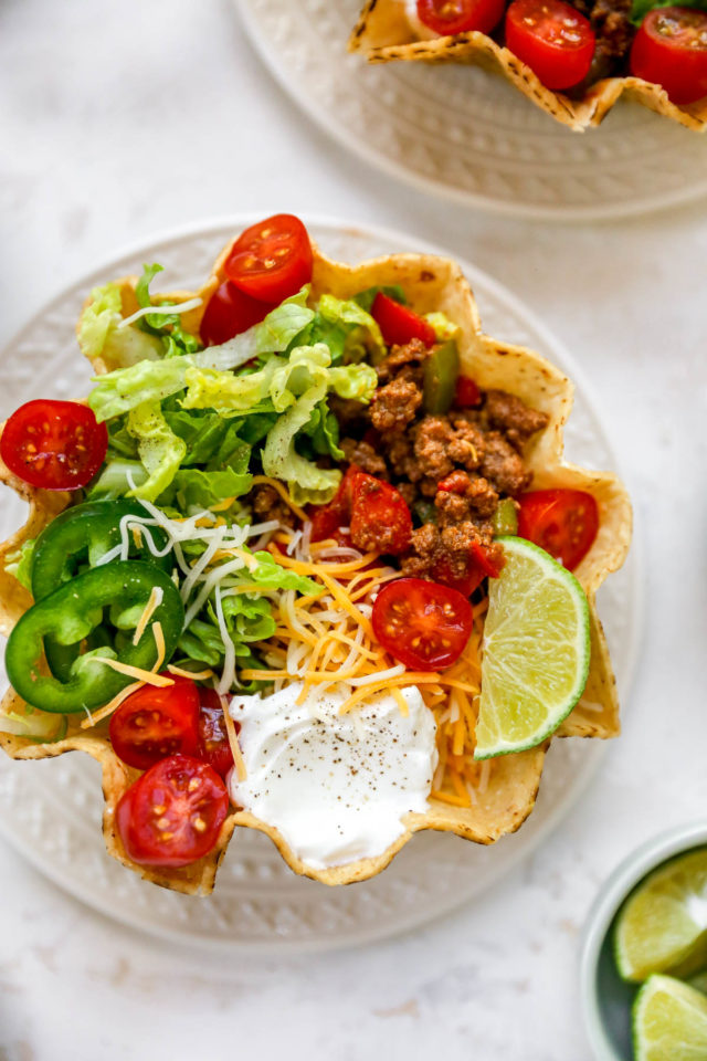 tostada filled with beef, lettuce, cheese and sour cream