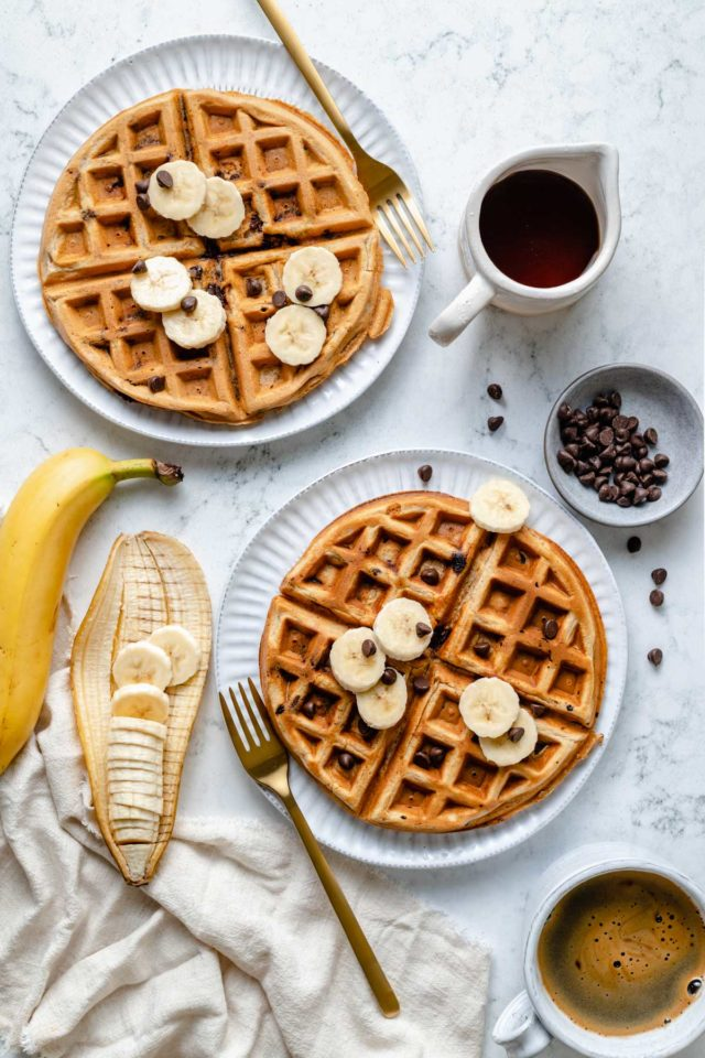 banana waffles served on white plates with sliced banana, chocolate chips and maple syrup