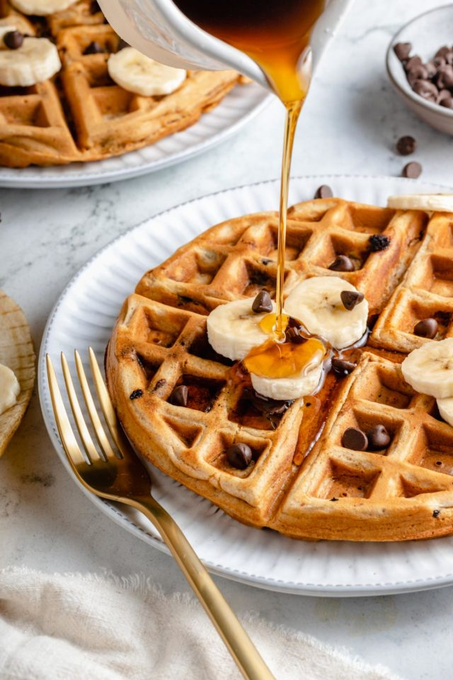 drizzling syrup over the top of chocolate chip waffles