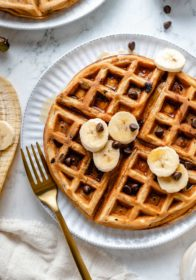 banana waffles topped with chocolate chips, banana slices and maple syrup