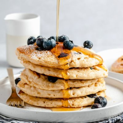 drizzling maple syrup over a stack of fluffy blueberry pancakes